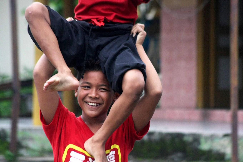 Teamwork: A barongsai dancer smiles as he lifts his partner. JP/ Maksum Nur Fauzan