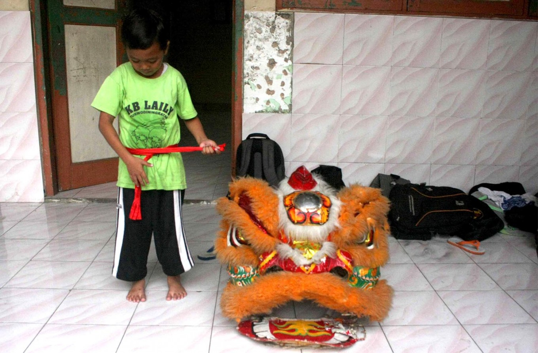 Secured: A barongsai dancer tightens his belt beside the iconic lion head. JP/ Maksum Nur Fauzan