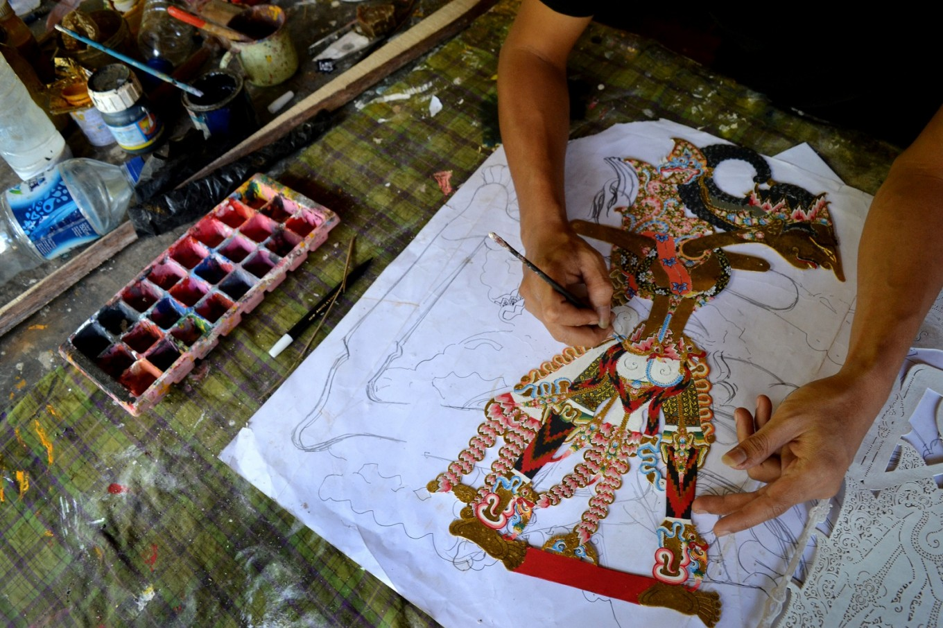 The 'sungging' process, where color is applied to the wayang kulit patterns using graduated colors.