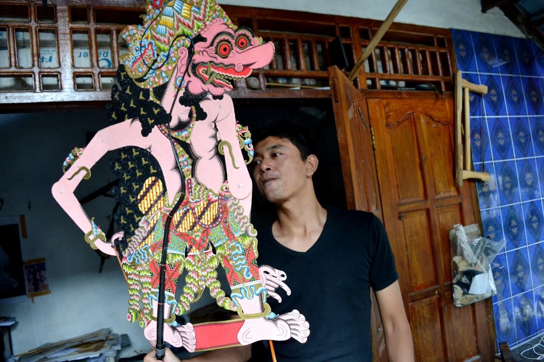 Totok Haryono, a craftsman from Kepuhsari, displays a finished 'wayang' charachter called Buto Raton.