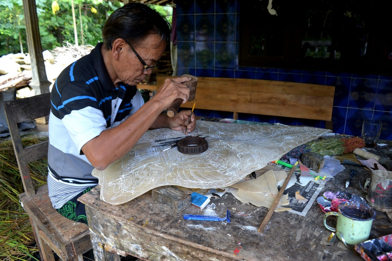 Wagimin, an experienced artisan of 'Tatah Sumbing' from Kepuhsari, passes own his skills to his children.