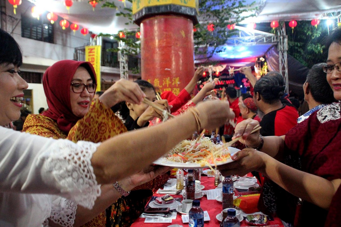 Semarang residents enjoy dinner at the tok panjang (long table) on the eve of Chinese New Year, locally known as Imlek. The main dishes are salad and fish. JP/Suherdjoko