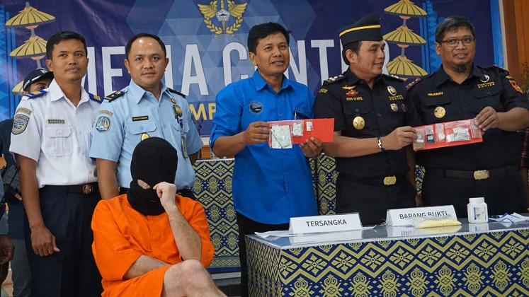 Drug presser: Customs and Excise Office personnel at Ngurah Rai International Airport show evidence allegedly confiscated from Siegfried Karl Achim Ruckel in a press conference on Feb. 22.