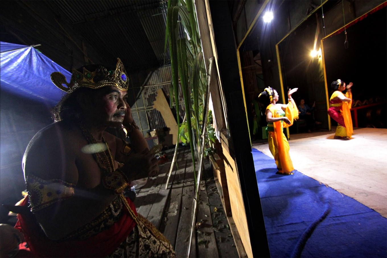 An actor gets ready while two dancers perform on stage. JP/Aditya Sagita