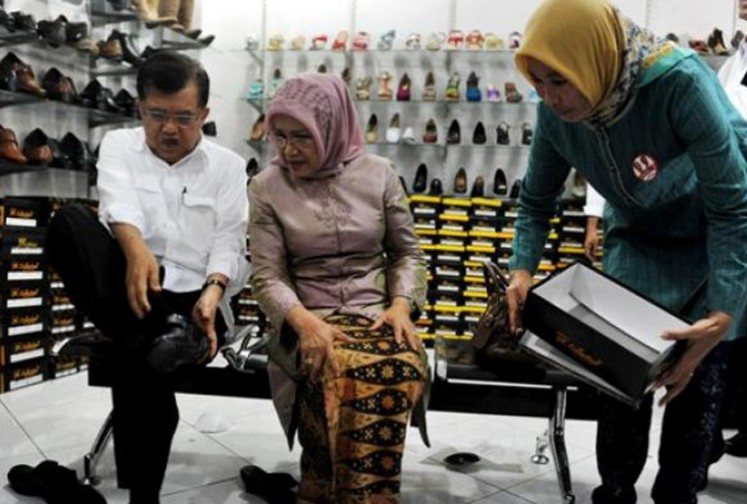 Vice President Jusuf Kalla, accompanied by his wife, Mufidah Jusuf Kalla, tries on shoes at a shoe store in Cibaduyut Market in Bandung, West Java.