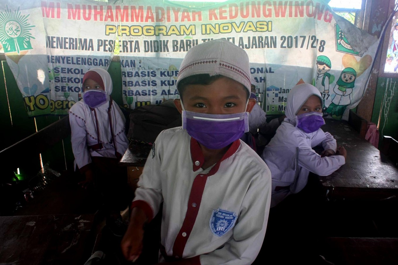 A boy's smile is hidden behind his surgical mask. JP/Maksum Nur Fauzan