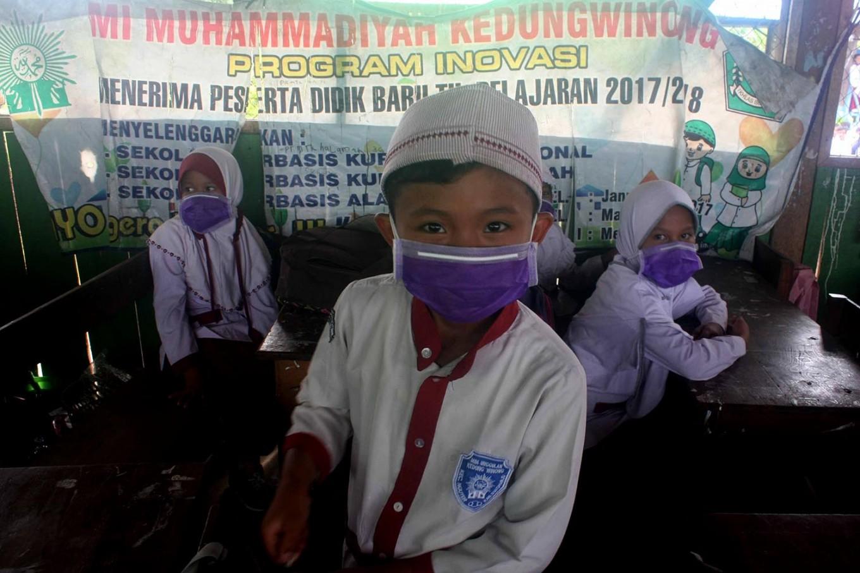 A boy's smile is hidden behind his surgical mask. JP/Maksum Nur Fauzan