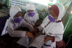 Three female students wear surgical masks while studying. JP/Maksum Nur Fauzan