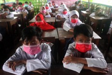 Muhammadiyah elementary school students wear surgical masks in class due to the strong smell from a nearby factory's chemical waste. JP/Maksum Nur Fauzan