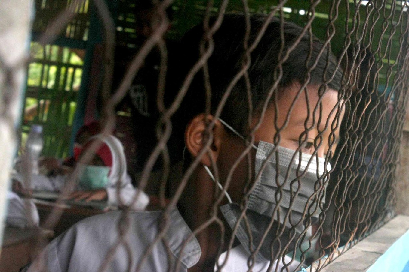 A boy looks outside the class window while wearing his surgical mask. JP/Maksum Nur Fauzan