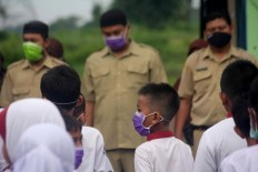 Teachers and students all wear surgical masks during the hoisting of the flag. JP/Maksum Nur Fauzan