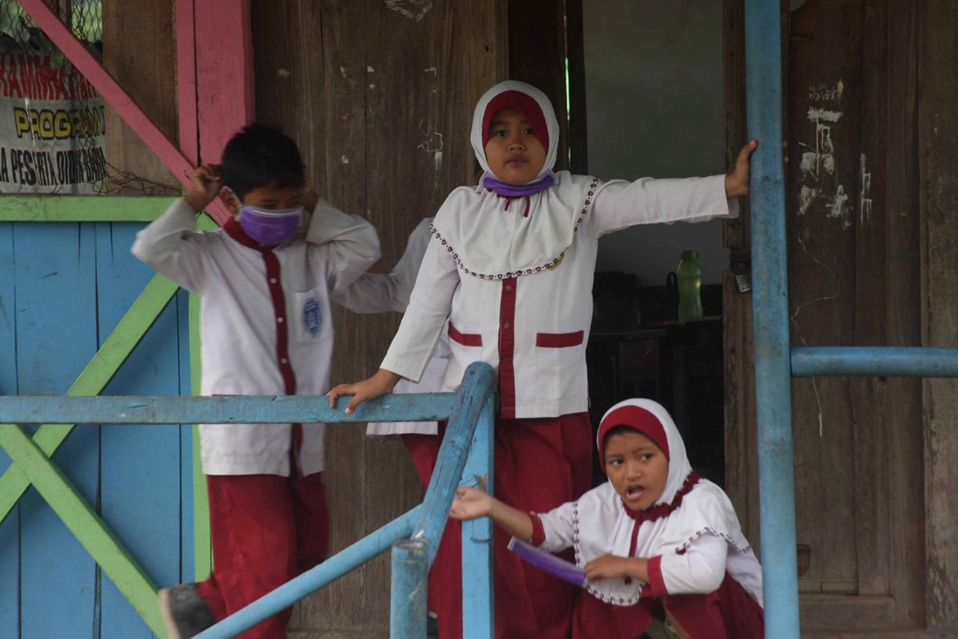 Two girls take off their surgical masks during a school break. JP/Maksum Nur Fauzan