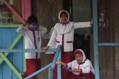 Two girls take off their surgical masks during a school break. JP/Maksum Nur Fauzan