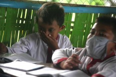 A boy covers his nose while his friend wears a surgical mask so they can focus on studying.JP/Maksum Nur Fauzan