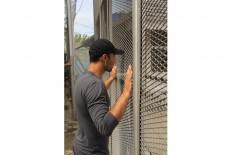 Let me in: A refugee takes a peak at the detention house. JP/ Rifky Dewandaru