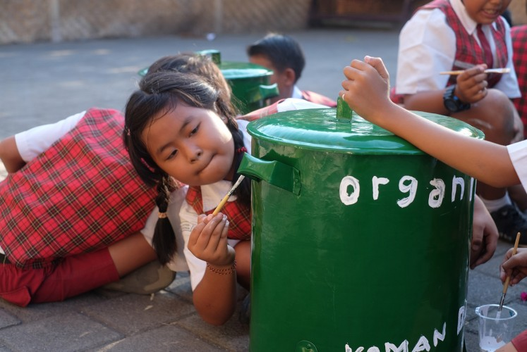 Students from local school paint on a trashcan.