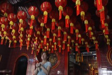 New Year spirit: A woman prays in the Dharma Bakti vihara in West Jakarta on Wednesday, February 14. The oldest Buddhist house of worship in the city, built in 1650, is decorated with red lanterns to welcome Imlek.JP/Ricky Yudhistira