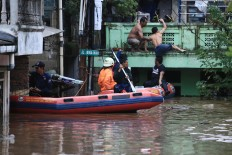 Search and rescue: Officials evacuate a resident from a flooded area in Rawajati, South Jakarta,on Monday, February 5. Heavy downpours that have struck Bogor and the mountainous Puncak area in West Java since Sunday night have caused flooding in areas along the Ciliwung river in Jakarta. JP/Dhoni Setiawan