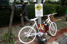 A pedestrian passes a memorial erected by the Rocketers cycling community dedicated to Raden Sandy Syafiek, a cyclist who died after being hit by a car on Saturday, February 10, on Jl Gatot Subroto in South Jakarta. The memorial is a reminder to road users to respect each other. JP/Wendra Ajistyatama