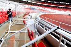Trail of vandalism: Acrylic barriers are under repair in Bung Karno Stadium in the wake of acts of vandalism by soccer supporters during the President's Cup final between Persija Jakarta and Bali United on the weekend. Match organizers reported around Rp 150 million (US$10,500) in damages. JP/Seto Wardhana
