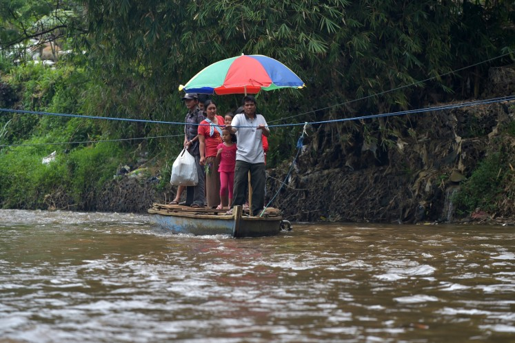 This picture taken on February 5, 2018 shows people crossing the Citarum river in a boat in Majalaya, West Java. Now faced with a health emergency after decades of failed clean-up efforts, Jakarta is stepping in with a seemingly impossible goal: make the Citarum river's water drinkable by 2025.