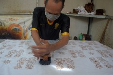 A worker prints batik with an ondel-ondel motif. JP/Endro Prakoso