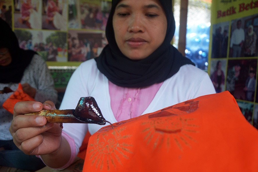 A woman draws a batik motif using the canting (copper pen filled with heated wax). JP/Endro Prakoso