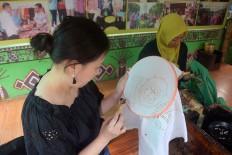 A Japanese visitor creates an orangutan motif. JP/Endro Prakoso