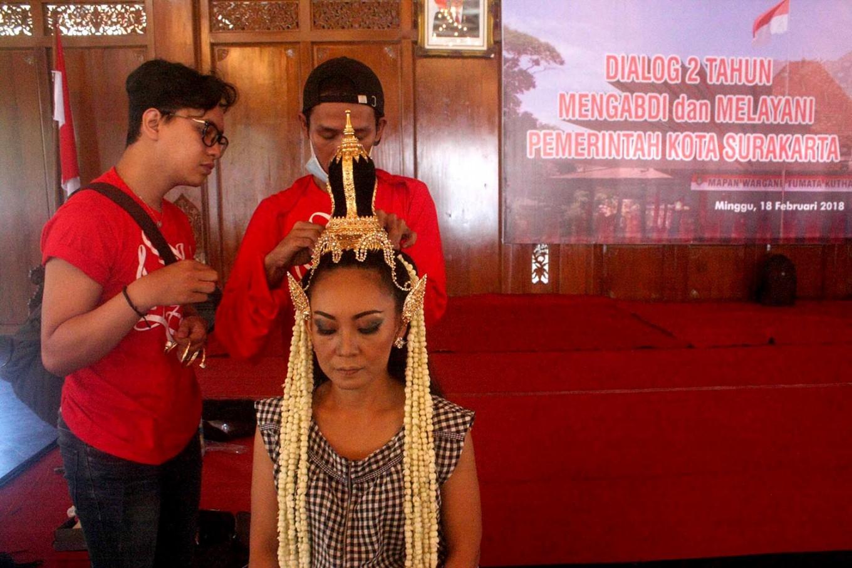 A female dancer is groomed by hairstylists. JP/Maksum Nur Fauzan