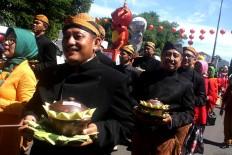 Civil servants wearing traditional Javanese attire carry 17 bowls of jenang (sticky rice porridge). [JP/Maksum Nur Fauzan