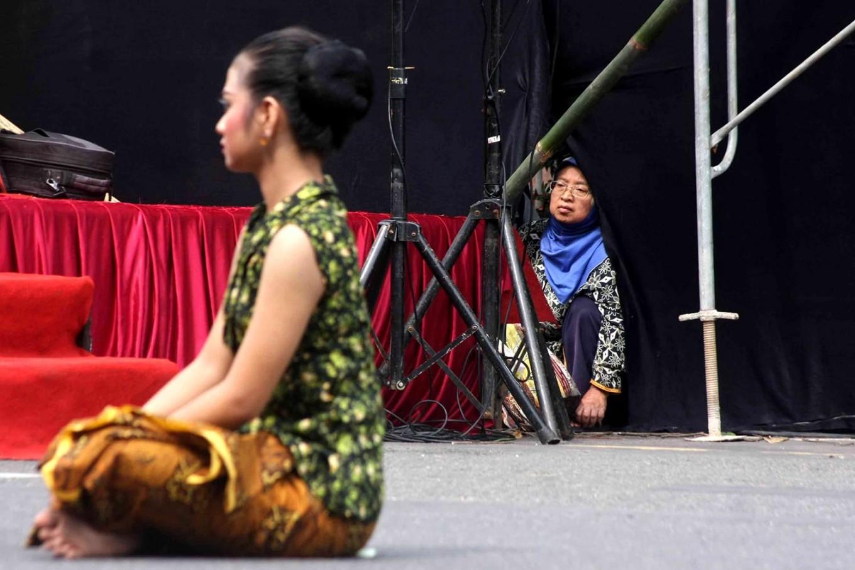 An elderly lady crouches on the asphalt to watch the performance. JP/Maksum Nur Fauzan