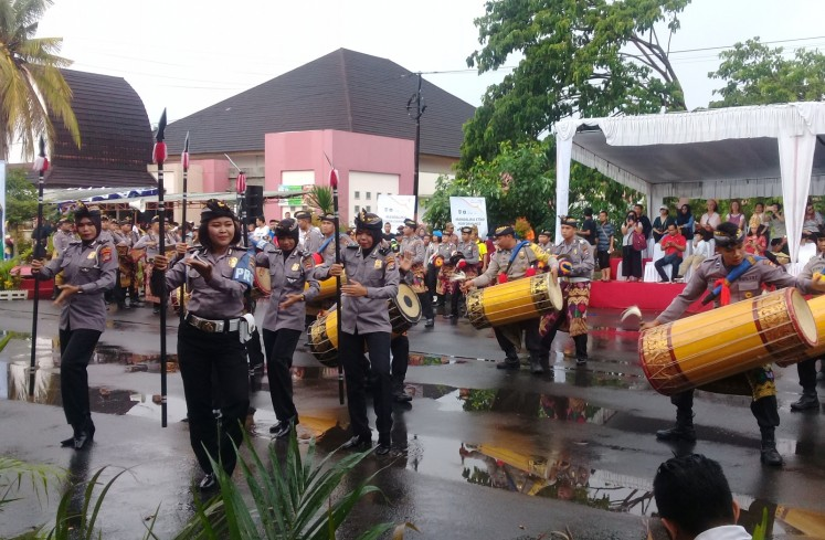 Members of the Central Lombok precinct police join the parade by playing