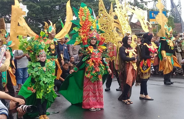 Participants of the parade walk down the street in Central Lombok.