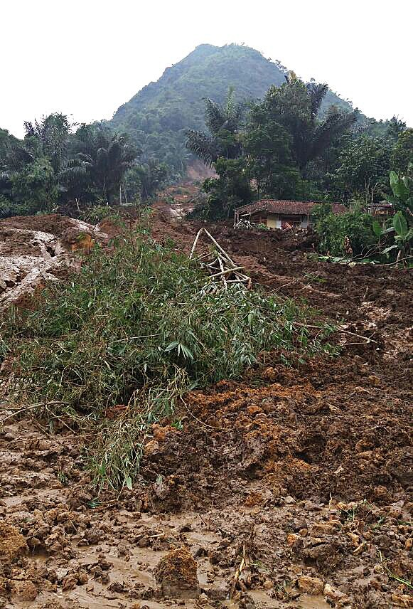 Buried: The mudslide engulfed four houses in Kampung Bonjot.