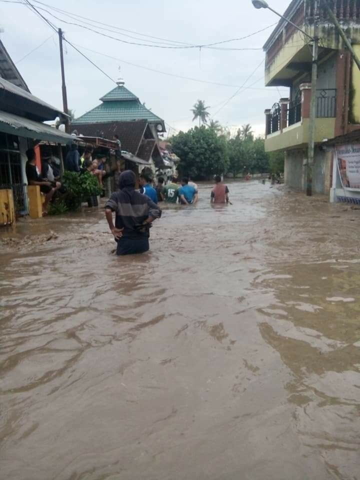 Inundated: Local residents pass through a flooded road in their village in Dompu regency, West Nusa Tenggara, on March 5.