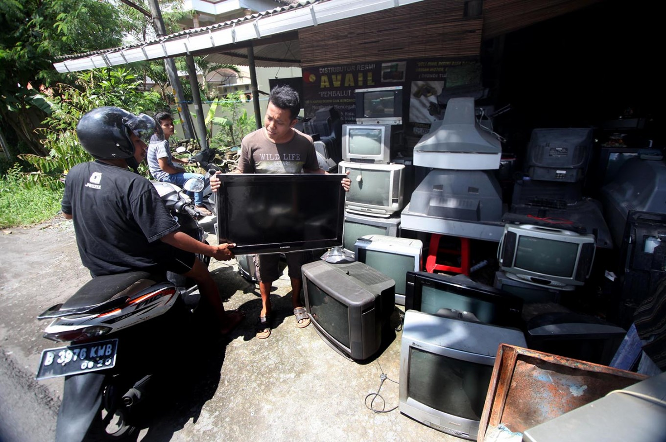 A customer comes to Sugeng's workshop have his flat screen TV set repaired. JP/Boy T. Harjanto