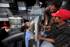 Supriyono (left) and Sugeng discuss how to repair a TV set. JP/Boy T. Harjanto
