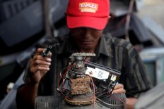 Supriyono is ready to repair a TV set. JP/Boy T. Harjanto
