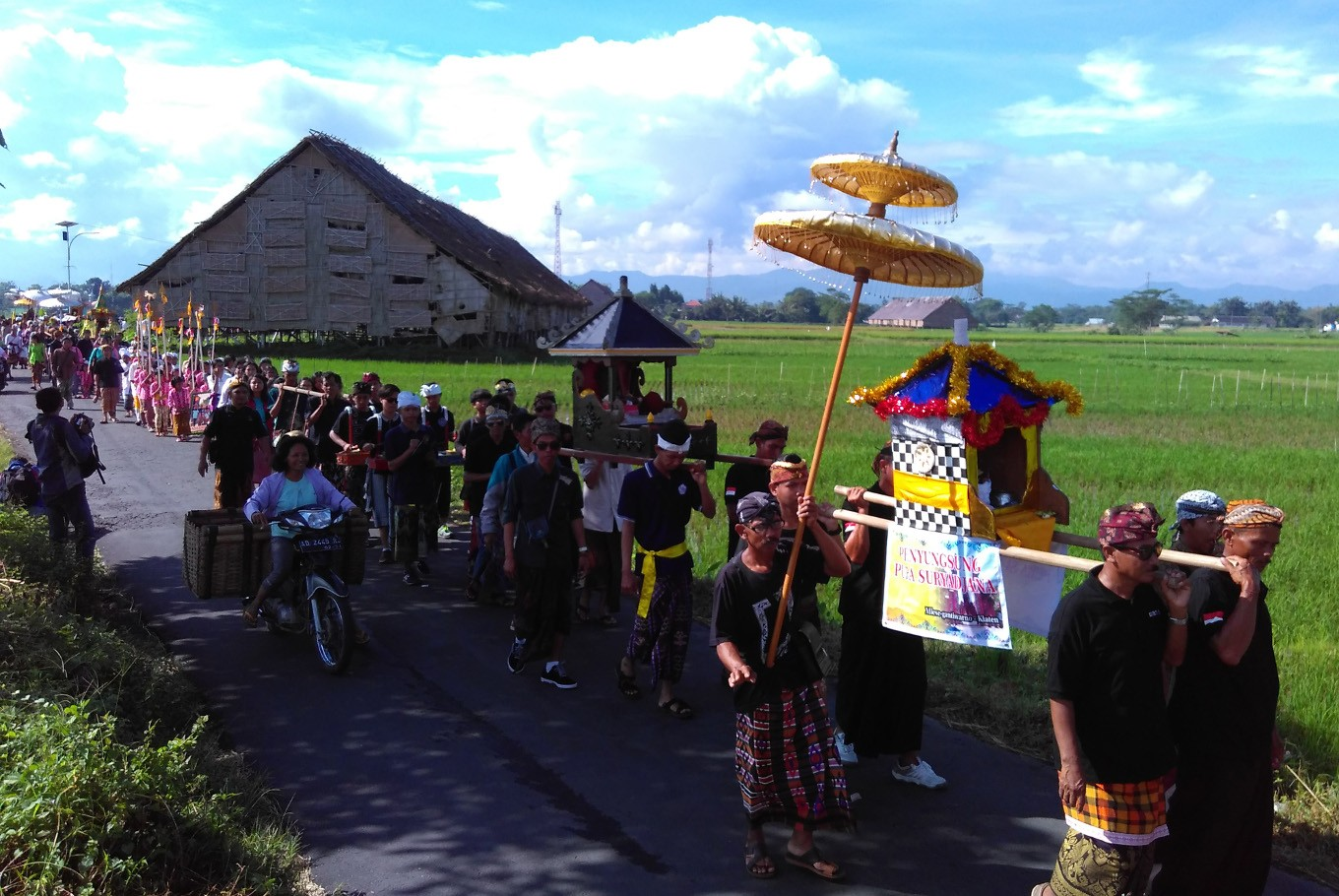 The parade is accompanied by gamelan Baleganjur. The participants bring offerings, including 'gunungan makanan' (cone-shaped float of offerings), 'ingkung' chicken, fruits and 'pratima' (sacred effigies). It is part of the Melasti ritual held in Klaten, Central Java, on Sunday, March 11.