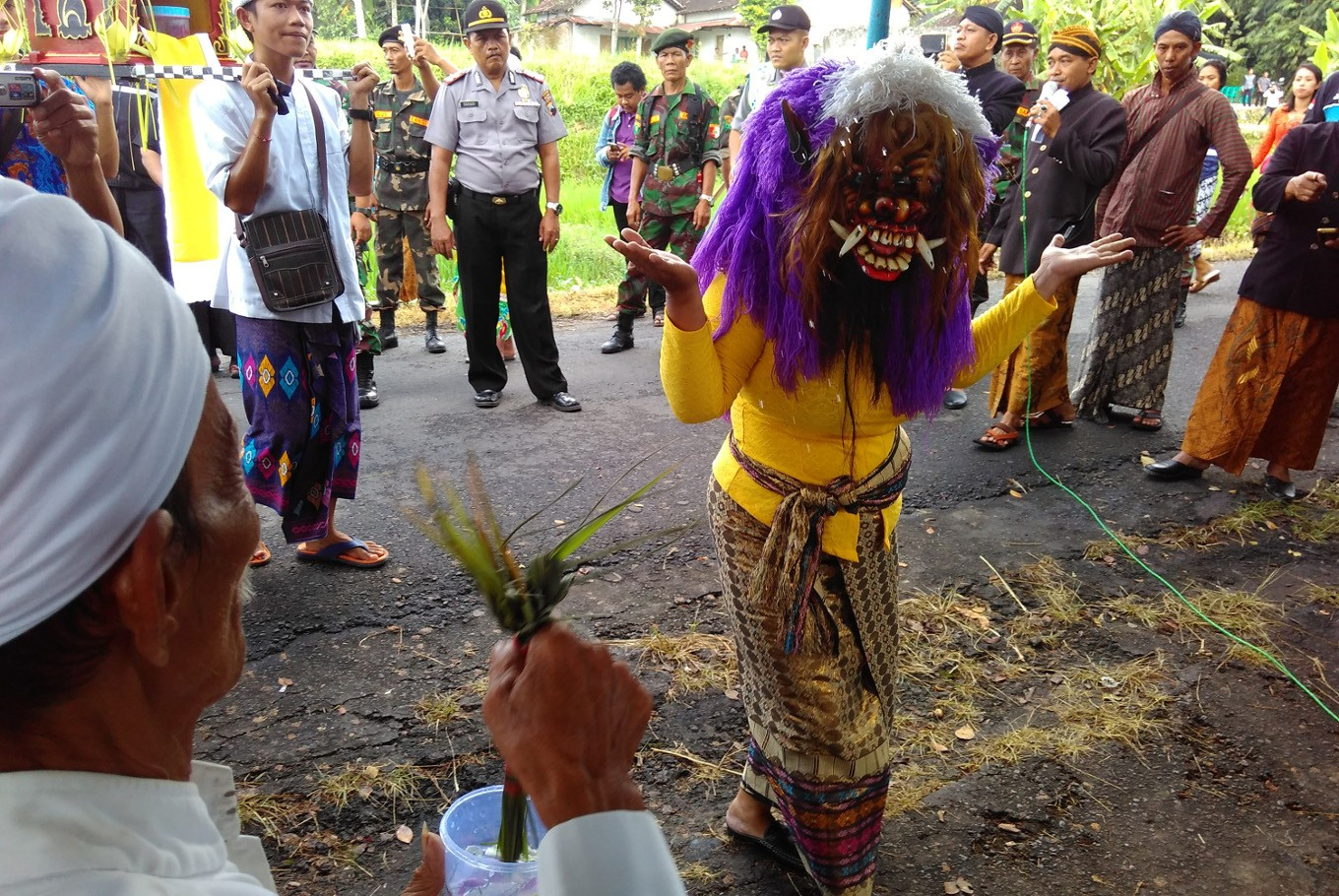 A Hindu woman wears a mask that symbolizes evil as she receives splashes of holy water from a priest during the Melasti ritual in Klaten, Central Java, on Sunday, March 11.