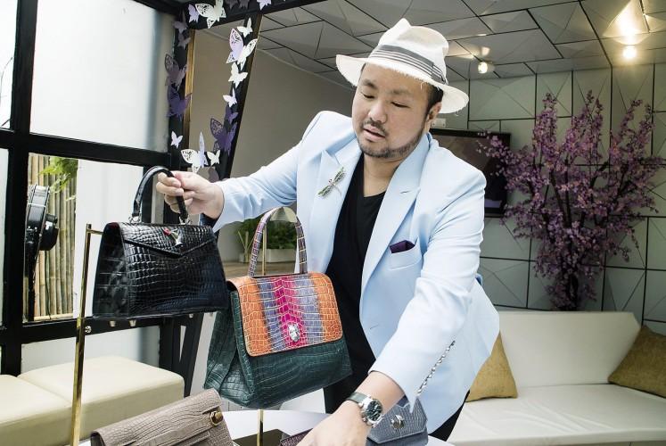 In style: Singaporean handbag designer Ethan Ko displays his designs.