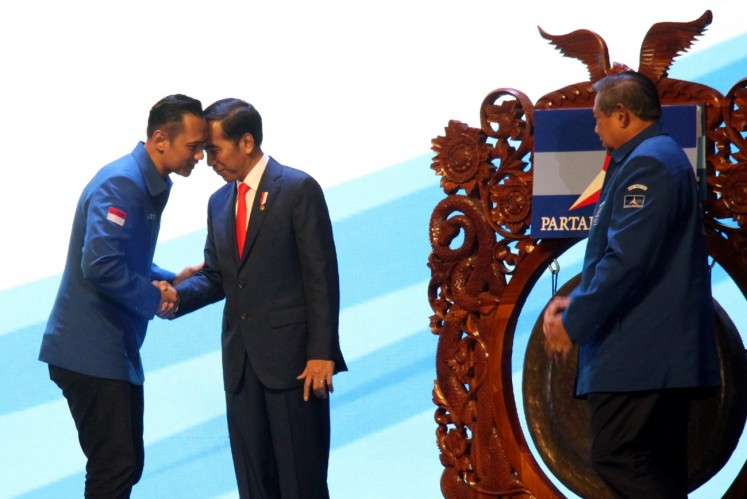President Jokowi (center) shakes hands with Democratic Party executive Agus Harimurti Yudhoyono (left), witnessed by party chairman Susilo Bambang Yudhoyono, during the opening of the party's 2018 national leaders meeting at Sentul International Convention Center (SICC) in Bogor, West Java, on March 10.