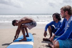 Wave riders: A foreign surfer and two locals prepare to hit the waves at Kuta Beach in Badung, Bali. JP/ Anggara Mahendra