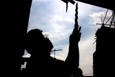"Blacksmith Subandi ""Bandi"" Suponingrat inspects one of his blades. JP/Maksum Nur Fauzan"