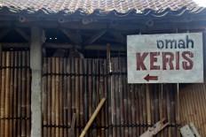 """A wooden board sign reads """"Omah Keris"""" (House of Kris) in front of Bandi's workshop. JP/Maksum Nur Fauzan"""