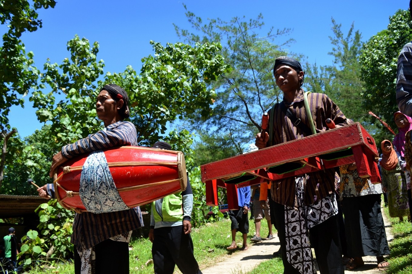 Villagers form a procession during the 'Sedekah Laut Ngalangi' ceremony to the accompaniment of 'bende' and 'kendang'.