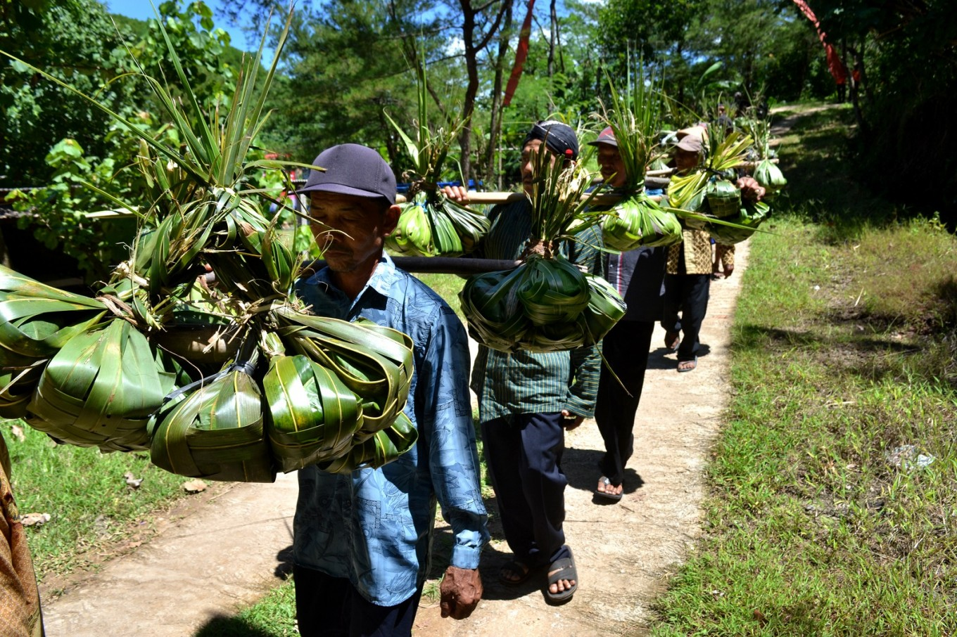 Jepitu villagers carry a variety of dishes wrapped in palm leaves for a communal feast during the 'Sedekah Laut Ngalangi' thanksgiving ceremony.