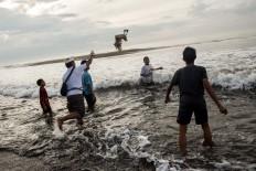 Into the waves: A man throws a duck into the ocean as an offering during Melasti. JP/Agung Parameswara