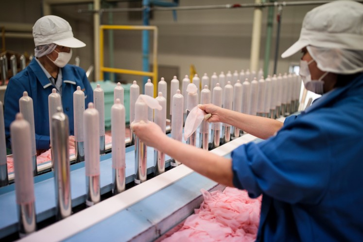 In this picture taken on January 25, 2018, employees of Japanese condom maker Sagami Rubber Industries perform quality tests for randomly picked condoms at the company's testing facility in Atsugi, Kanagawa prefecture.