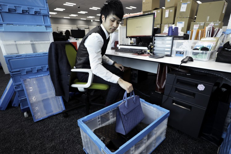 A SOU employee checks a used Louis Vuitton bag at the company office in Tokyo.
